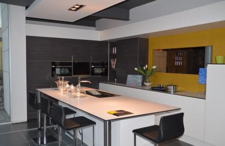 cuisine blanche avec armoire en bois foncé et mur jaune