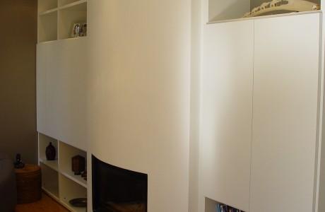 chauffage au bois de couleur blanc et de forme convex accompagné d'armoire de chaque côté